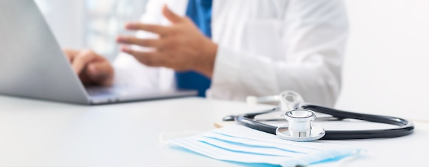 Online-medizin-konzept. stethoskop und medizinische maske am arbeitsplatz des arztes im hintergrund. der arzt führt eine online-patientenberatung mit einem laptop durch