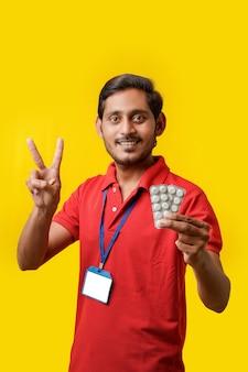 Online-medizinkonzept: indischer lieferbote, der medizinstreifen in der hand hält