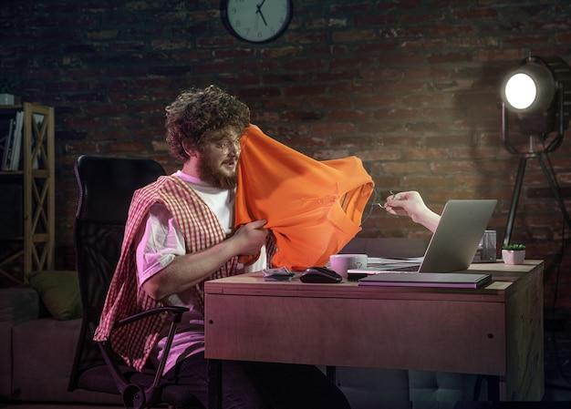 Online-meeting, chat, videoanruf. junger mann, der zu hause mit einem freund online über einen laptop spricht. virtuelle realität. konzept der sicheren fernunterhaltung, besprechungen während der quarantäne. platz kopieren