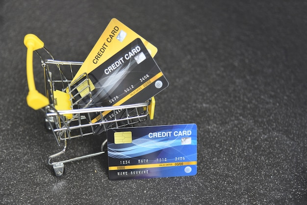 Online mit kreditkarte in einem warenkorb auf dem dunklen hintergrund für online-zahlung zu hause kaufen