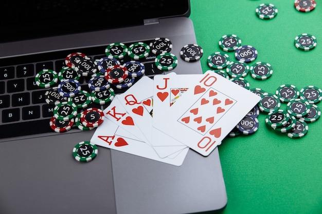 Online poker casino thema. glücksspielchips, spielkarten und laptop auf grünem hintergrund.