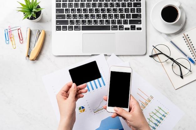 Online-rechnungszahlungskonzept, eine frau, die nachgebildete kreditkarte und handy auf büroschreibtisch lokalisiert auf marmorhintergrund, kopienraum, draufsicht, flatlay, nahaufnahme verwendet