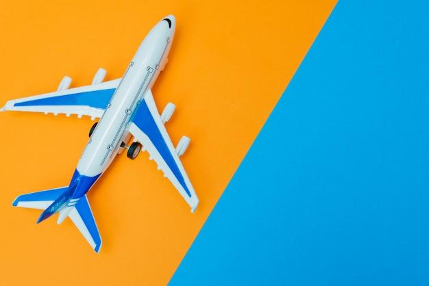 Online-reisebuchungskonzept. flugzeugmodell und reisepass auf gelbem und orangefarbenem hintergrund. abstrakte landebahn