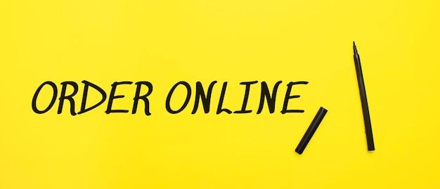 Online-schild mit schwarzem marker auf gelbem grund bestellen. mit kopienraum bereit für ihren text.