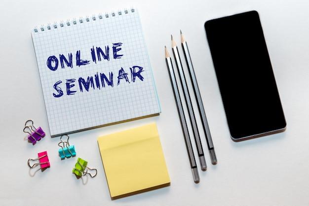 Online-seminar eine inschrift, eine phrase, die in einem notizblock geschrieben ist und mit einem smartphone und stiften auf einem hellen hintergrund liegt.
