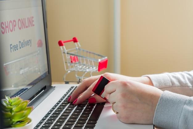 Online-shop auf dem laptop-bildschirm. kostenlose lieferung. e-commerce-konzept. kaukasische frau kaufen online von zu hause aus mit bankkarte für die zahlung