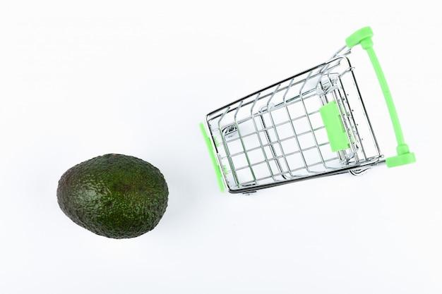 Online-shop. wagen und avocado auf weiß