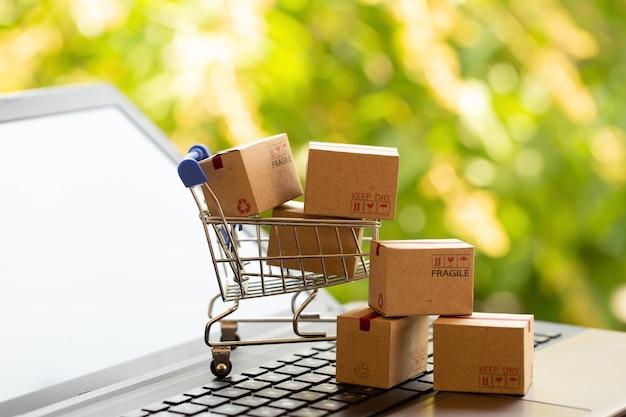 Online-shopping, e-commerce-konzept boxen in einem einkaufswagen auf einer laptoptastatur