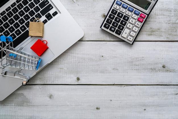Online-shopping-hintergrund mit einkaufswagen-papiertüten auf laptop und taschenrechner auf weißem schreibtisch