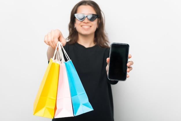 Online-shopping ist besser. junge frau hält einige papiertüten und ihren telefonbildschirm.