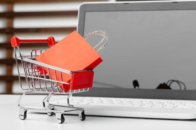 Online-shopping-konzept. einkaufswagen, laptop auf dem schreibtisch