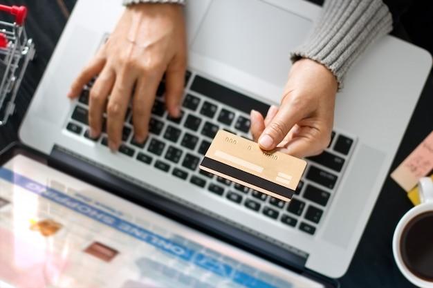 Online-shopping-konzept. frau, die in der hand goldkreditkarte und das on-line-einkaufen hält