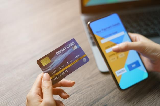 Online-shopping-konzept. frau hände halten kreditkarte und mit kreditkarte online-shopping.