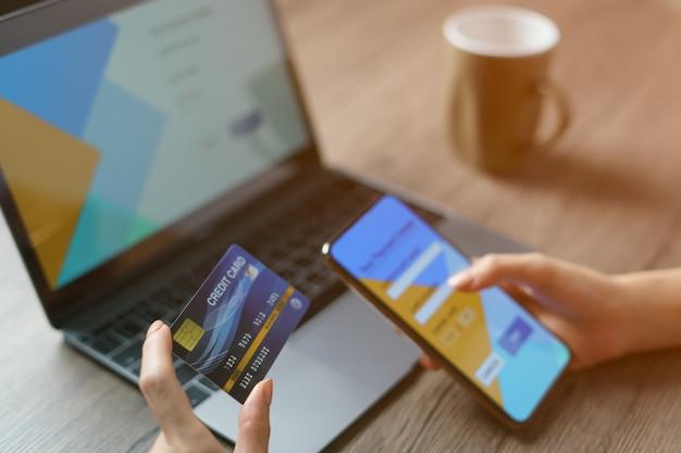 Online-shopping-konzept: frauenhände halten cradit und verwenden es für online-shopping