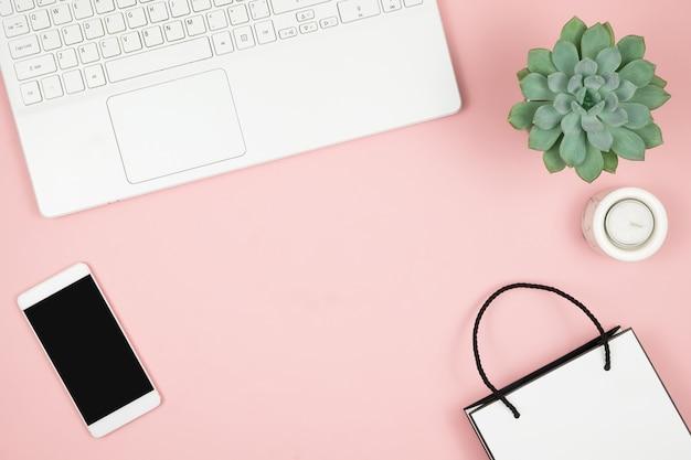 Online-shopping-konzept. frauenhände mit telefon und laptop auf rosa oberfläche. draufsicht, kopierraum.