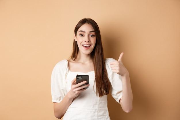 Online-shopping-konzept glückliche junge frau, die daumen hoch zeigt und handy lächelnd erfreut stand...