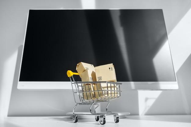 Online-shopping-konzept. kleiner einkaufswagen mit vielen papierboxen
