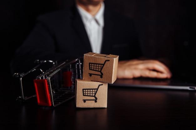 Online-shopping-konzept. laptop mit mini-marktwagen und zwei boxen