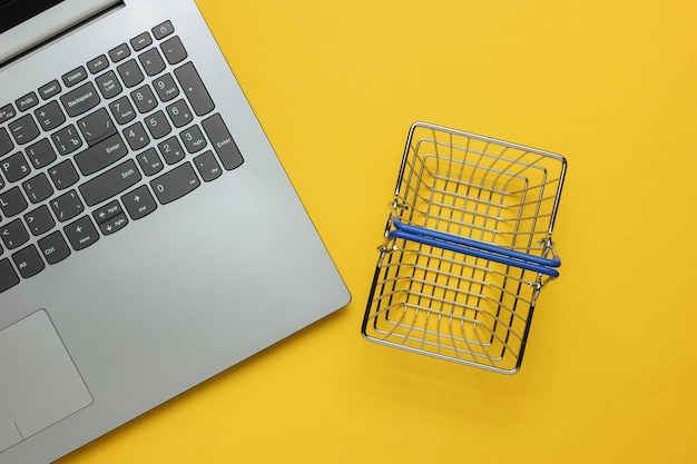 Online-shopping-konzept laptop und mini-einkaufskorb