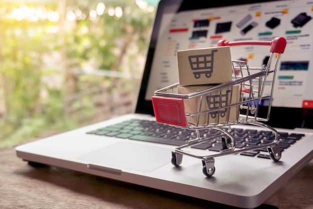 Online-shopping-konzept - paket- oder papierkartons mit einem einkaufswagenlogo in einem trolley auf einer laptoptastatur. einkaufsservice im online-web. bietet hauszustellung an.