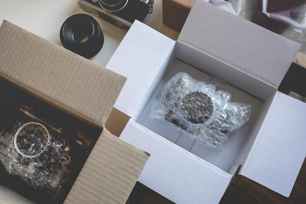 Online-shopping-konzepte mit produkt in box auf schreibtisch tisch