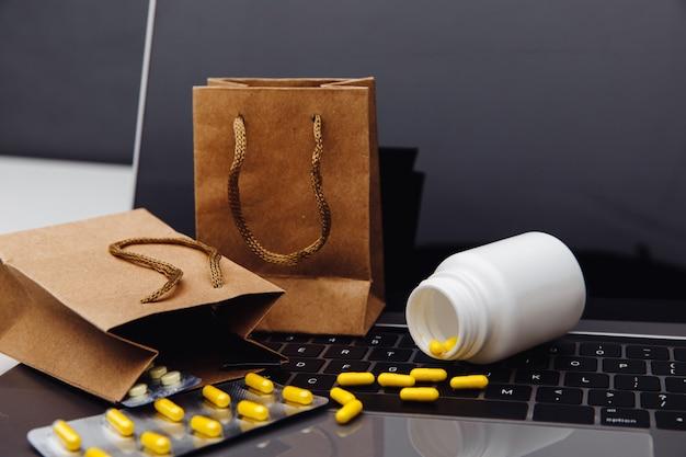 Online-shopping mit lieferung nach hause. taschen mit pillen auf tastatur und medizinischen instrumenten.