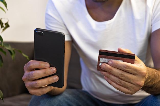 Online-shopping-modell. mann online bestellung mit dem telefon und kreditkarte von zu hause aus bezahlen