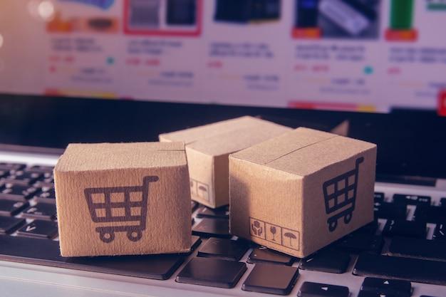 Online-shopping - papierkartons oder paket mit einem warenkorb-logo auf einer laptop-tastatur. einkaufsservice im internet und bietet lieferung nach hause.
