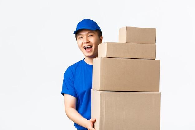 Online-shopping, schnelles versandkonzept. freundlicher lächelnder junger asiatischer männlicher kurier in blauer uniform trägt kisten mit bestellungen. lieferbote bringt pakete zu ihrer haustür, stehender weißer hintergrund.