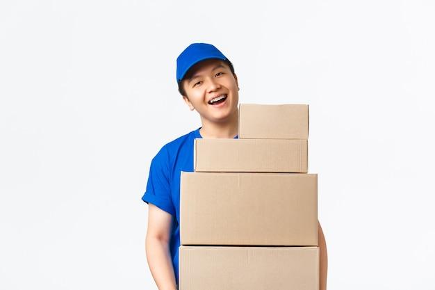 Online-shopping, schnelles versandkonzept. fröhlicher lächelnder asiatischer liefermann in blauer kurieruniform, der kisten mit aufträgen hält, pakete zum kundenhaus trägt, freudiger weißer hintergrund steht.