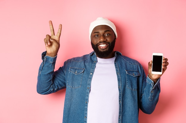 Online-shopping und technologiekonzept. fröhlicher schwarzer typ in mütze und jeanshemd mit mobilem bildschirm und friedenszeichen, stehend über rosa hintergrund