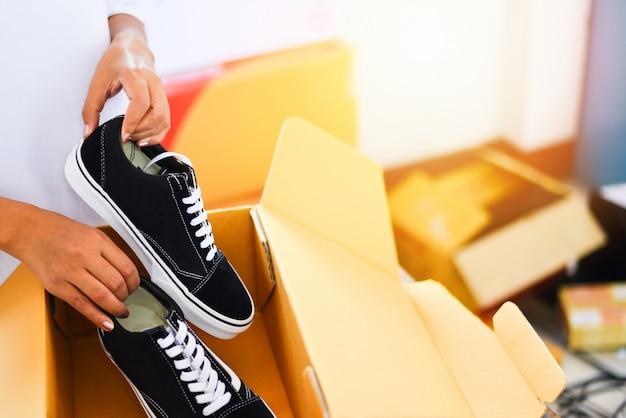 Online-shopping verkaufen. frauenverpackungs-schuhturnschuhe in der pappschachtel bereiten paketkasten zum zustelldienst vor.