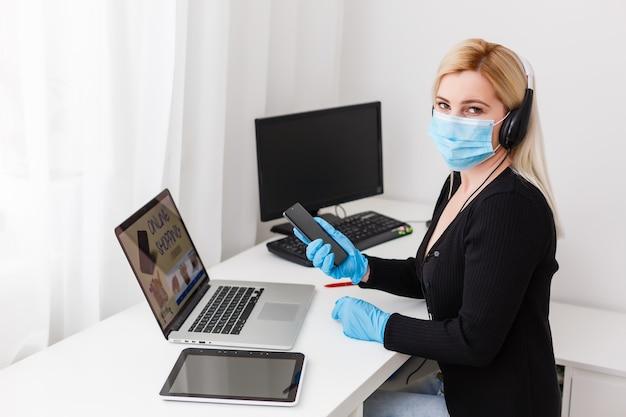 Online-shopping während der coronavirus-quarantäne. frau in schutzmaske zu hause, freier raum