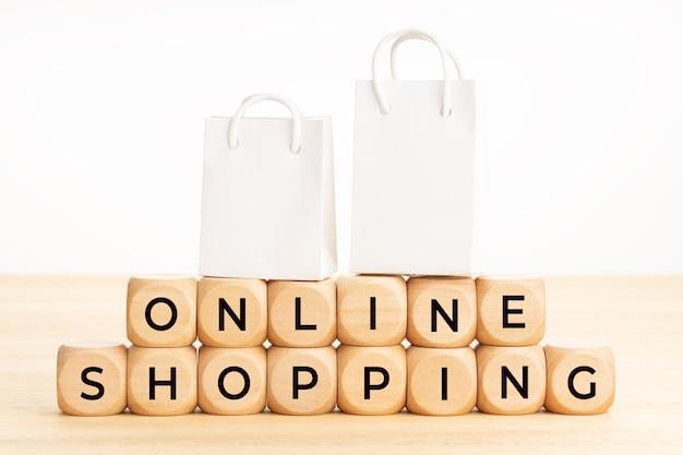 Online-shopping-wörter auf holzklötzen auf tisch und papier-einkaufstüten