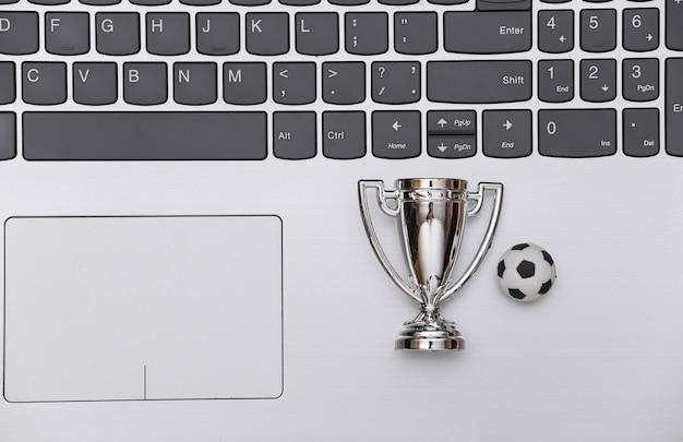 Online-sportwetten. fußball und meisterpokal auf laptoptastatur. ansicht von oben. flach legen