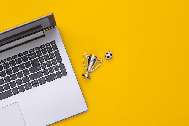 Online-sportwetten. laptop, fußball und meisterpokal auf gelbem hintergrund mit kopienraum. ansicht von oben. flach legen