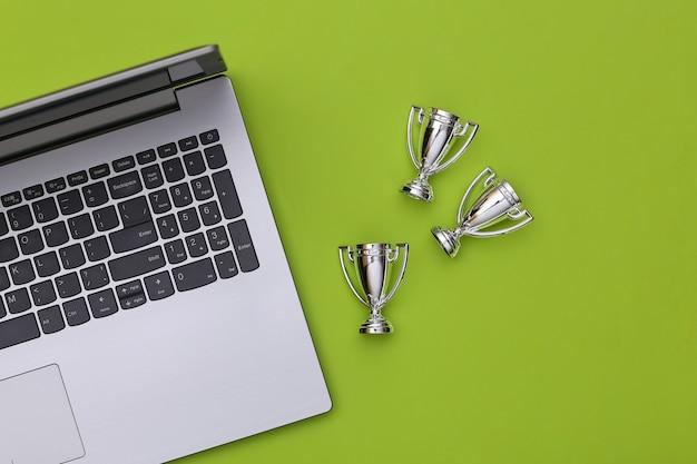 Online-sportwetten. laptop- und meisterschaftsbecher auf grünem hintergrund. ansicht von oben. flach legen