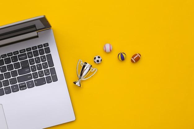 Online-sportwetten. laptop, unterschiedlicher sportball und meisterpokal auf gelbem hintergrund mit kopienraum. ansicht von oben. flach legen