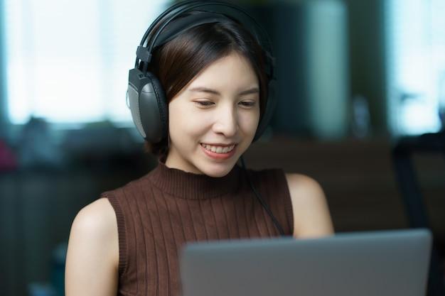 Online-trainingskonzept: frau in kopfhörern, die computer, schüler oder lehrer betrachten, die per videokonferenz sprechen.
