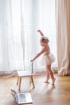 Online-unterricht. das kleine mädchen ist mit ballett beschäftigt. tanzen. zuhause.