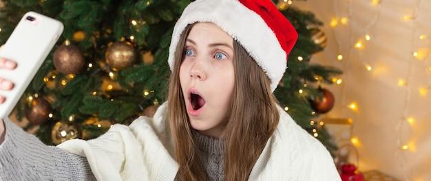 Online weihnachtseinkauf. schockiertes junges mädchen in der weihnachtsmütze halten handy