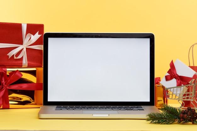 Online-weihnachtseinkaufskonzept auf laptop-anzeige. weißer bildschirm auf computer und geschenke mit papiertüten nahe.