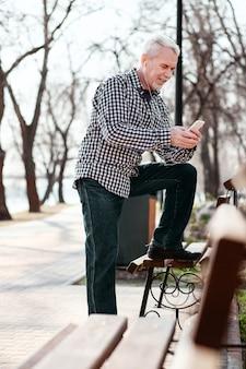 Online-wiedergabeliste. niedriger winkel des nachdenkens des älteren mannes, der telefon benutzt und musik hört