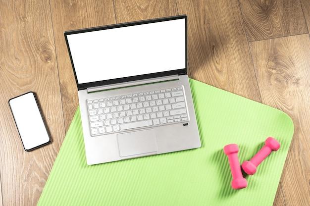 Online-yoga-fitness, laptop-modell. rosa hanteln, gymnastikmatte und grauer laptop auf holzboden. online-trainingskonzept.