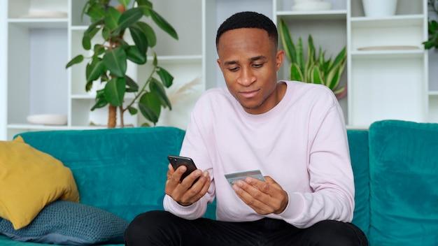 Online-zahlung afroamerikanischer mann, der kreditkarte hält und smartphone für das einkaufen im internet zu hause verwendet