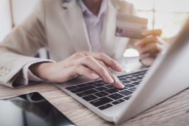 Online-zahlung, die hand des jungen mannes unter verwendung des computerlaptops und hand, die kreditkarte für das on-line-einkaufen hält.