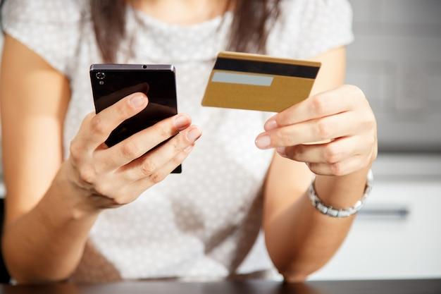Online-zahlung, hände der frauen, die eine kreditkarte halten und intelligentes telefon für das on-line-einkaufen verwenden
