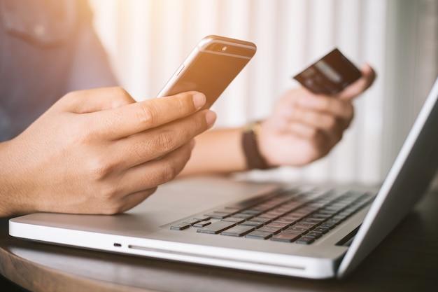 Online-zahlung, hände des mannes, die smartphone halten und kreditkarte für das on-line-einkaufen verwenden.
