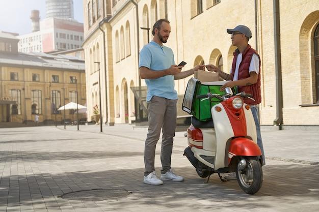 Online-zahlung junger fröhlicher mann, der papiertüte mit essen erhält