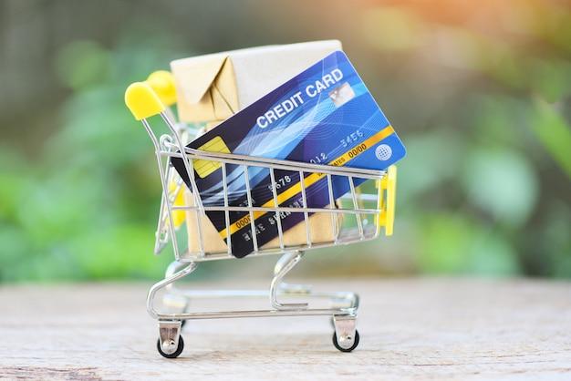 Online-zahlung kreditkarte und paketboxen im warenkorb. online-shopping-technologie und kreditkartenzahlungskonzept